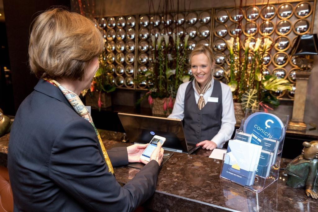 Kölns Oberbürgermeisterin Henriette Reker demonstrierte persönlich die Möglichkeiten der neuen Technologie bei einer Live-Vorführung im Savoy Hotel. Beim Betreten wurde der Meldeschein automatisch ausgedruckt. Ein händisches Ausfüllen war nicht mehr nötig. Foto: Cornelis Gollhardt
