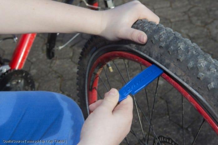 Mit speziellen Reifenhebern ? am besten aus Kunststoff und ohne scharfe Kanten ? wird der Mantel an einer Seite des Reifens aus der Felge gehebelt. copyright: www.pd-f.de / Kay Tkatzik