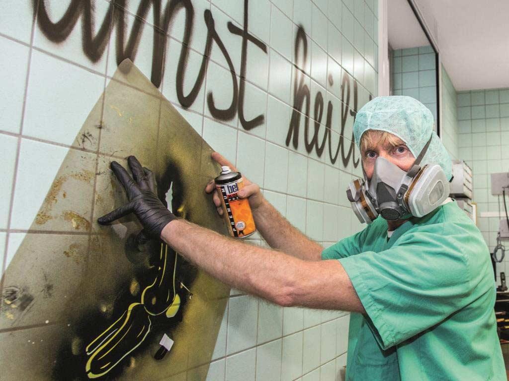 """Der Bananensprayer kreierte das weltweit erste OP-Graffiti im Operationssaal des Gemeinschaftskrankenhauses Bonn, anlässlich der dortigen Ausstellung """"Medizinischer Block"""". copyright: Atelier Baumgärtel"""