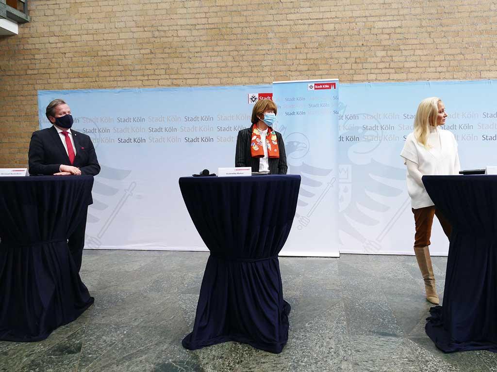 Auf einer Pressekonferenz stellten Christoph Kuckelkorn (links), Kölner Oberbürgermeisterin Henriette Reker (Mitte) und Künstlerin Janine Kunze (rechts) die Planungen zur Sessionseröffnung in der Rheinmetropole vor.